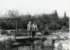 Foto af Jutta og Peter Ottesen stående ved rækværket på en bro over vandløbet fra en lille sø i deres smukke have.