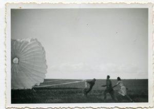 3 personer trækker i snorene til en faldskærm