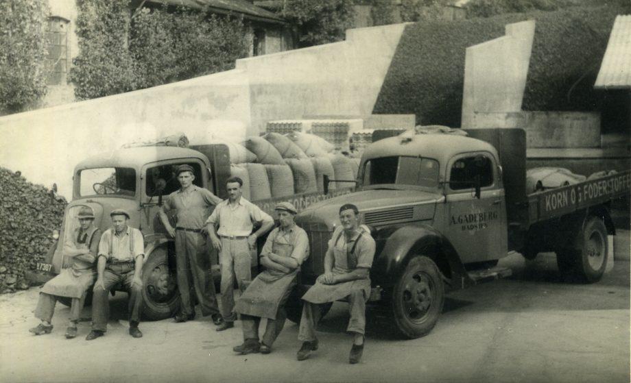 Chauffører og medarbejdere stående foran firmats lastbiler