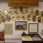 Væg med udstilling om Hadsten Bank: Ovale rammer med portrætter af direktørerne. Indrammet første aktie. Gl. rentesatser. Foto af banken m.m.